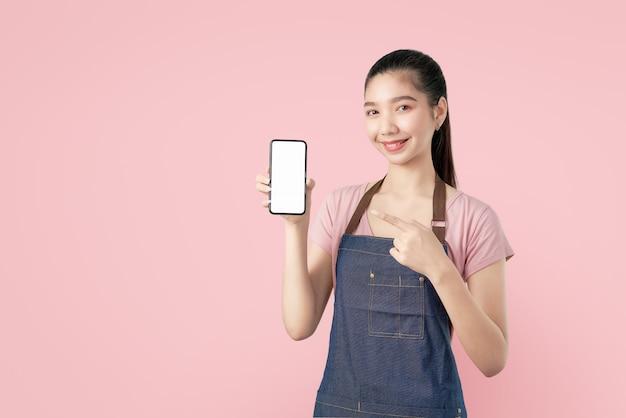 Lächelnder leerer bildschirm des asiatinshow smartphone der junge mit dem zeigen des fingers. Premium Fotos