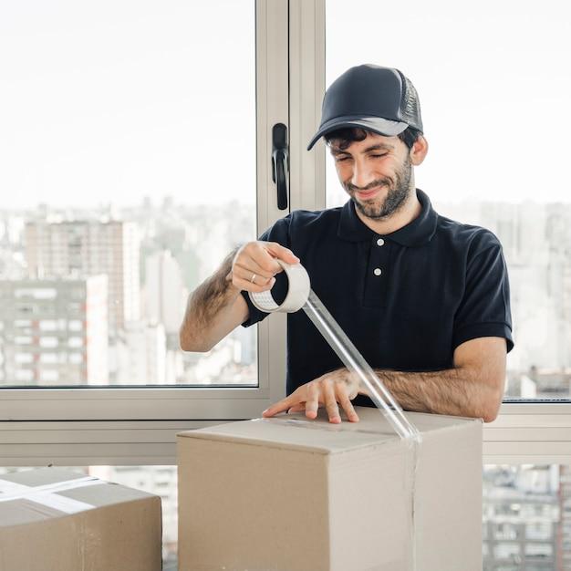 Lächelnder lieferer in der einheitlichen verpackungspappschachtel Kostenlose Fotos