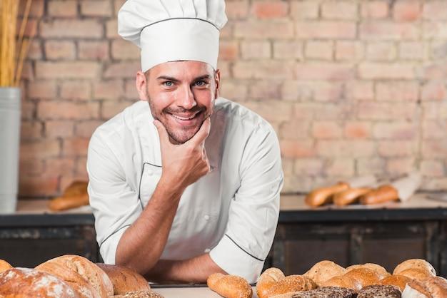 Lächelnder männlicher bäcker an der bäckerei Kostenlose Fotos