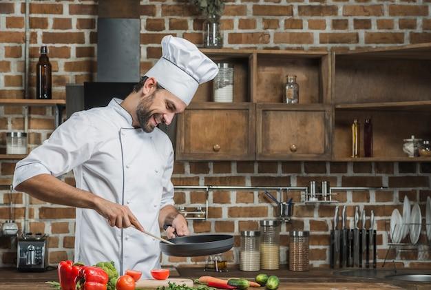Lächelnder männlicher chef, der lebensmittel in der küche zubereitet Kostenlose Fotos