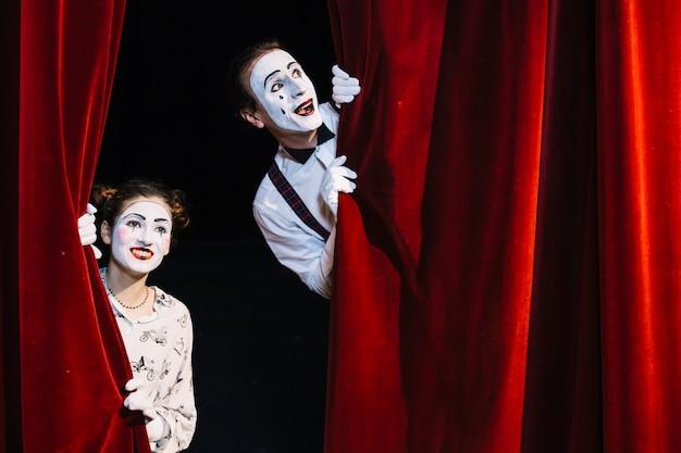 Lächelnder männlicher und weiblicher pantomimekünstler, der vom roten vorhang späht Kostenlose Fotos