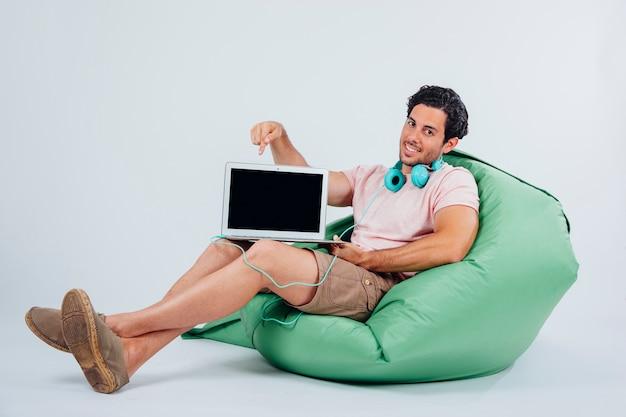 Lächelnder mann auf couch zeigt laptop Kostenlose Fotos