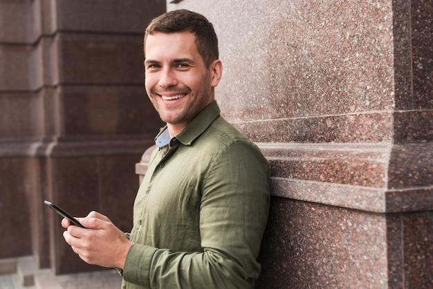 Lächelnder mann, der auf der wand hält mobiltelefon sich lehnt und kamera betrachtet Kostenlose Fotos