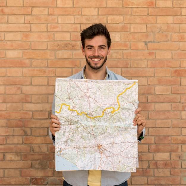 Lächelnder mann, der eine offene karte hält Kostenlose Fotos