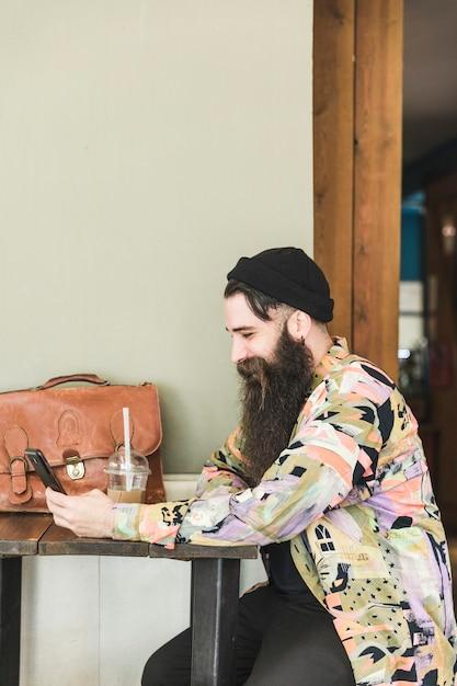 Lächelnder mann, der im café unter verwendung des handys sitzt Kostenlose Fotos