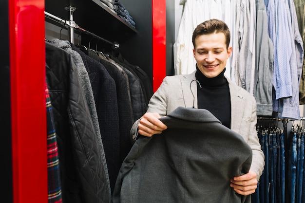 Lächelnder mann, der jacke in einem shop wählt Kostenlose Fotos