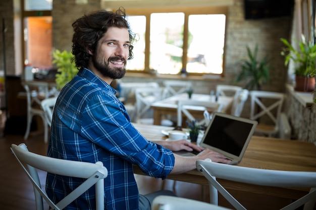 Lächelnder mann, der laptop in der kaffeestube mit Kostenlose Fotos