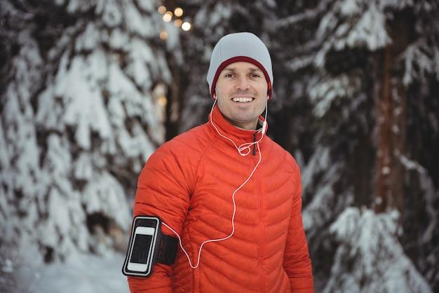 Lächelnder mann, der musik in kopfhörern vom smartphone hört Kostenlose Fotos