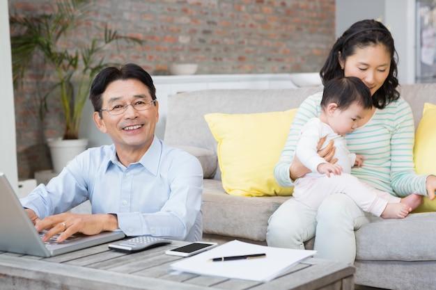 Lächelnder mann, der rechnungen im wohnzimmer zählt, während frau mit babytochter spielt Premium Fotos