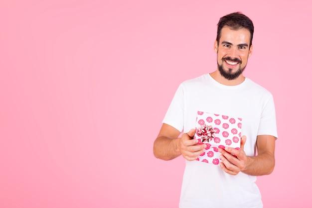Lächelnder mann, der rosa blumengeschenkbox gegen rosa hintergrund hält Kostenlose Fotos