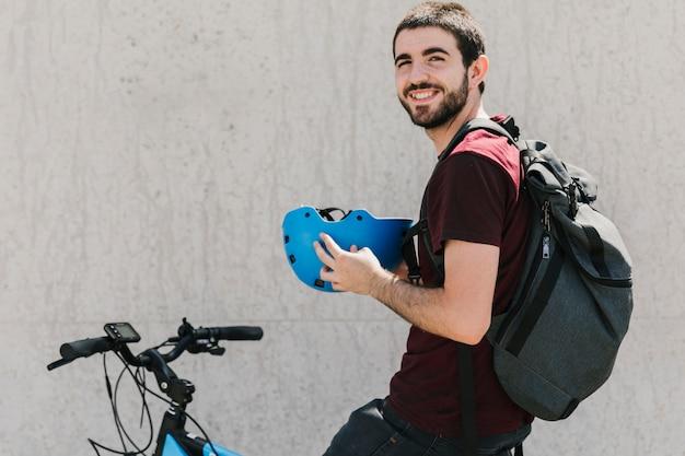 Lächelnder mann, der sturzhelm auf fahrrad hält Kostenlose Fotos