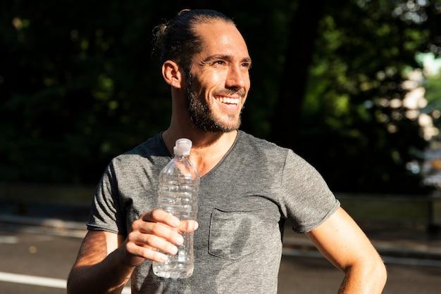 Lächelnder mann, der wasserflasche hält Kostenlose Fotos