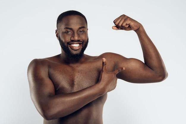 Lächelnder mann des afroamerikaners mit bloßem kasten. Premium Fotos