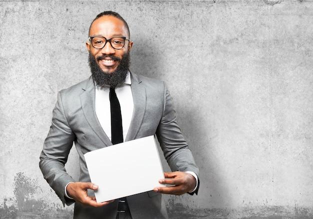 Lächelnder mann im anzug mit einem weißen kasten Kostenlose Fotos