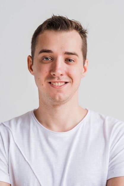 Lächelnder mann im weißen t-shirt auf grauem hintergrund Kostenlose Fotos