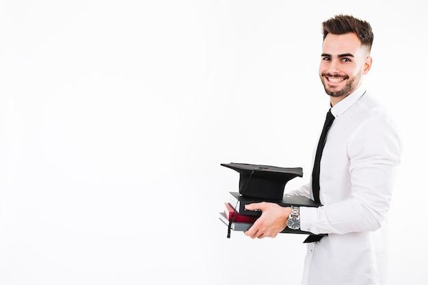 Lächelnder mann mit büchern und doktorhut Kostenlose Fotos