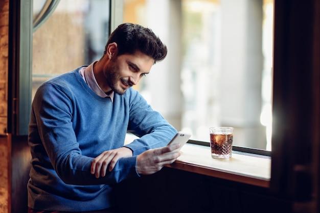 Lächelnder mann mit der blauen strickjacke, die seinen smartphone in einer modernen kneipe betrachtet. Premium Fotos