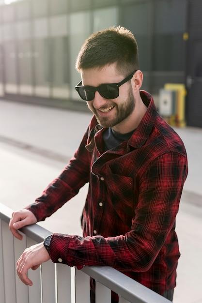 Lächelnder mann mit der sonnenbrille, die auf zaun sich lehnt Kostenlose Fotos