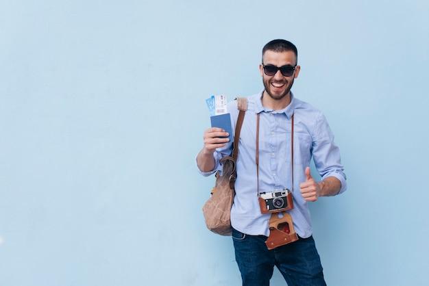 Lächelnder mann mit kamera um seinen hals, der flugticket hält und daumen herauf die geste steht nahe blauer wand zeigt Kostenlose Fotos