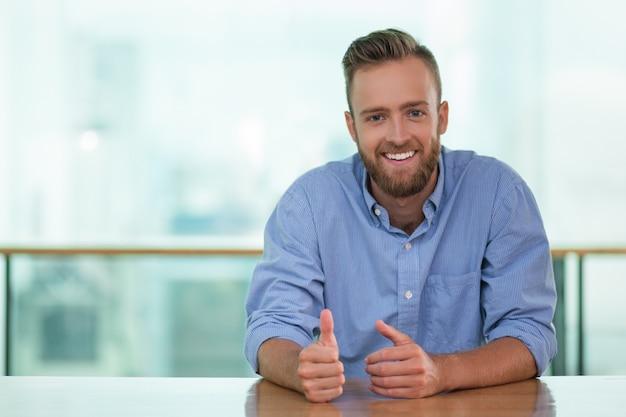 Lächelnder mann sitzt am tisch eines cafes und gestikulieren Kostenlose Fotos