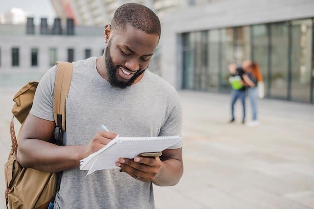 Lächelnder mann student mit docs Kostenlose Fotos