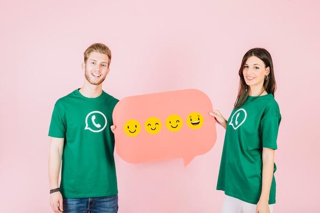 Lächelnder mann und frau, die spracheblase mit verschiedener art von emoticons halten Kostenlose Fotos