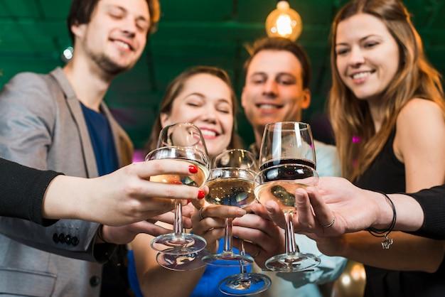 Lächelnder mann und freundinnen, die cocktails in der party an der bar rösten Kostenlose Fotos