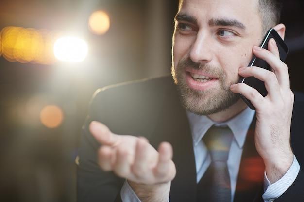 Lächelnder moderner geschäftsmann talking by smartphone Kostenlose Fotos
