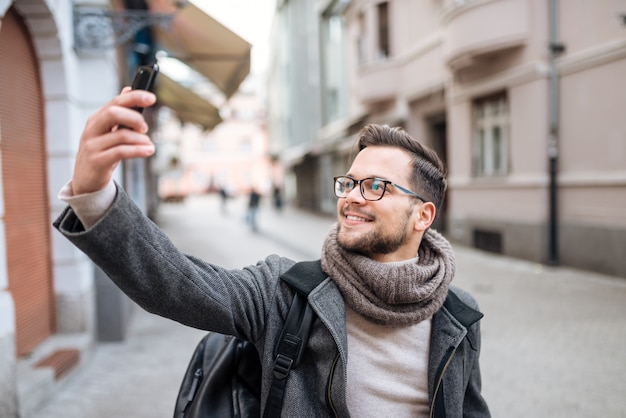 Lächelnder modischer junger mann, der selfie in der winterstadt nimmt. Premium Fotos
