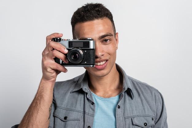 Lächelnder mulattemann, der ein retro- photocamera gegen sein gesicht hält und die kamera betrachtet Premium Fotos