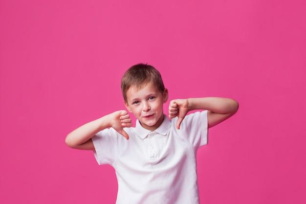 Lächelnder netter junge, der abneigungsgeste über rosa wand zeigt Kostenlose Fotos