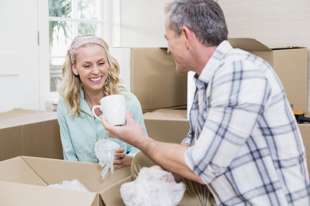 Lächelnder paarverpackungsbecher in einem kasten zu hause Premium Fotos