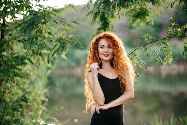 Lächelnder redhead draußen hintergrundbeleuchtet durch sonne, modetrieb. Premium Fotos