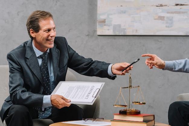 Lächelnder reifer männlicher rechtsanwalt, der in der hand vertrag in der hand gibt ihrem kunden stift hält Kostenlose Fotos
