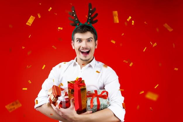 Lächelnder reizend hübscher hippie-mann-kerl des parteikonzeptes des neuen jahres glücklicher spaß, der die winterweihnachtsfeiertage tragen hirschhornhutholding feiert, stellt kastengeschenk goldene konfettis dar Premium Fotos