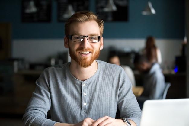 Lächelnder rothaarigemann mit dem laptop, der kamera im café betrachtet Kostenlose Fotos