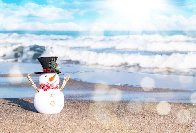 Lächelnder schneemann am sonnigen strand. feiertagskonzept für karten der frohen weihnachten und des guten rutsch ins neue jahr Premium Fotos