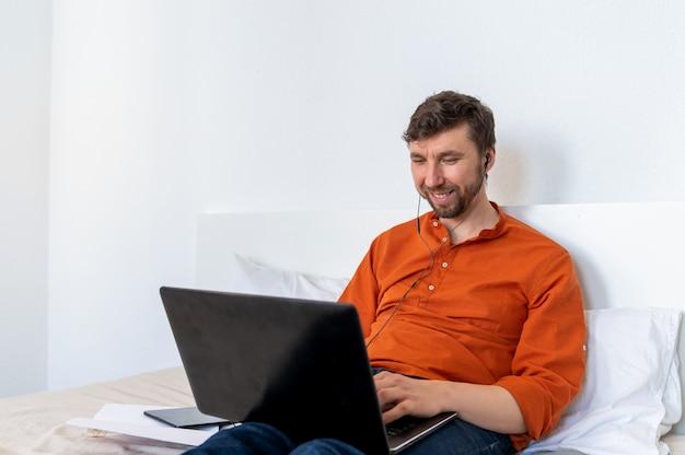 Lächelnder schöner mann, der laptop zu hause benutzt Premium Fotos
