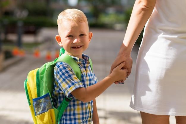 Lächelnder schüler, der mutter-hand hält Premium Fotos