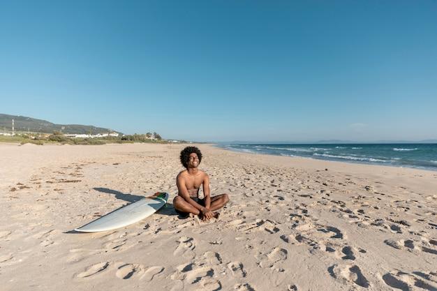 Lächelnder schwarzer mann, der auf strand sich entspannt Kostenlose Fotos
