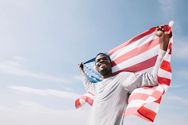 Lächelnder schwarzer mann, der hinten zurück wellenartig bewegende amerikanische flagge hält Kostenlose Fotos