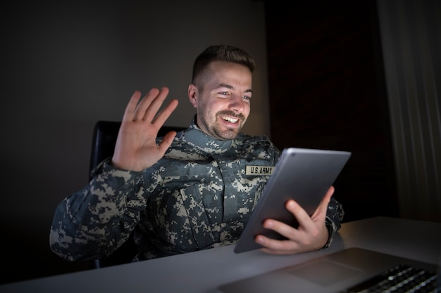 Lächelnder soldat in militäruniform, der über einen tablet-computer mit seiner familie wiedervereinigt wird Kostenlose Fotos