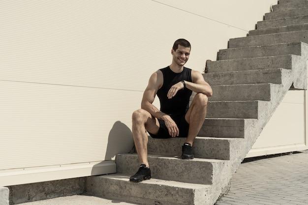 Lächelnder sportler, der am fuß der aufsteigenden treppe sitzt Kostenlose Fotos