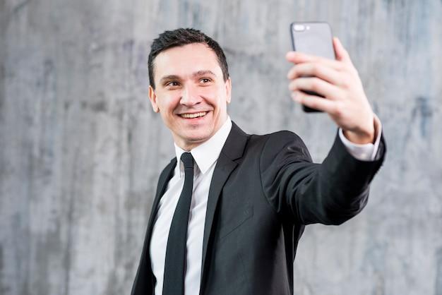 Lächelnder stilvoller geschäftsmann, der selfie mit smartphone nimmt Kostenlose Fotos