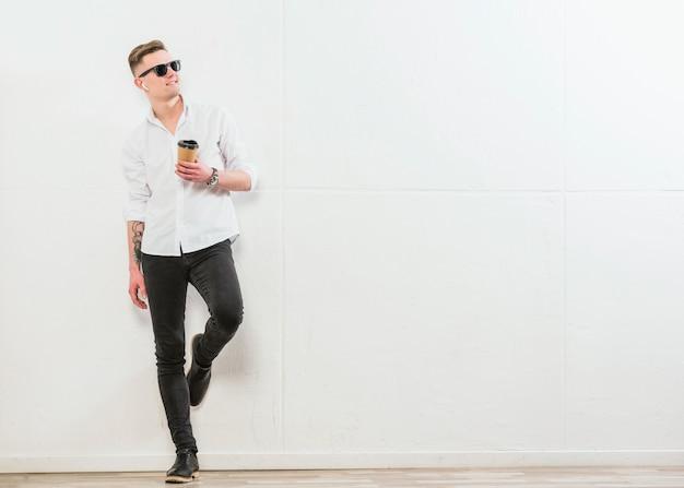 Lächelnder stilvoller junger mann, der die wegwerfkaffeetasse zum mitnehmen steht gegen weiße wand hält Kostenlose Fotos