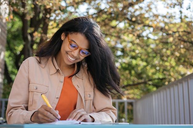Lächelnder student, der lernt, sprachen lernt, schreibt, bildungskonzept Premium Fotos