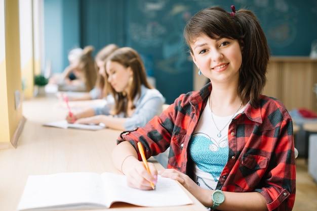 Lächelnder student mit notizblock im unterricht Kostenlose Fotos