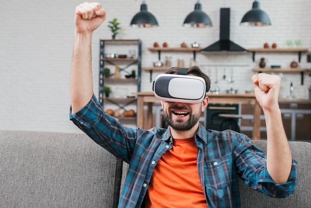 Lächelnder tragender google der virtuellen realität des jungen mannes, der seine faust zusammenpreßt Kostenlose Fotos
