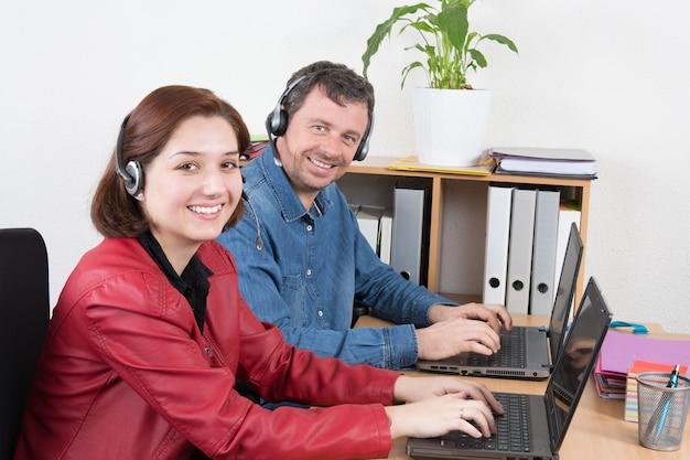 Lächelnder tragender kopfhörer des weiblichen und männlichen kundendienstmitarbeiters mit den kollegen, die im hintergrund im büro arbeiten Premium Fotos