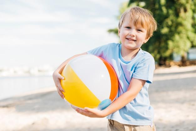 Lächelnder tragender wasserball des jungen beide hände Kostenlose Fotos